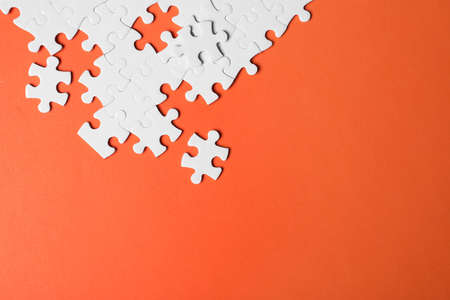 Blank white puzzle pieces on orange background, flat lay. Space for text