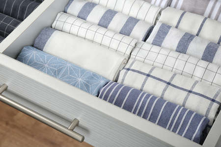 Open drawer with folded towels, closeup. Order in kitchen