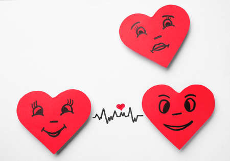 Paper hearts with drawn faces on white background, top view. Concept of jealousy