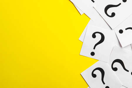 Paper notes with question marks on yellow background, flat lay. Space for text