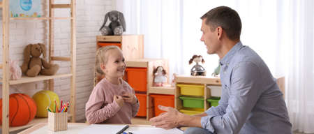 Child psychotherapist working with little girl in office