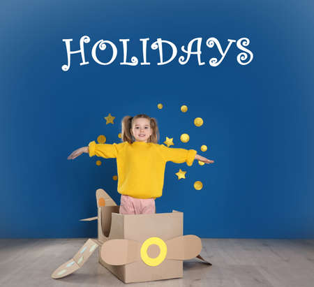 School holidays. Cute little child playing with cardboard plane near blue wall 免版税图像