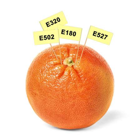 Fresh orange with E numbers isolated on white. Harmful food additives  版權商用圖片