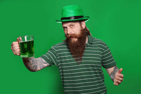 Bearded man with green beer on color background. St. Patrick's Day celebration