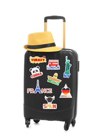 Modern suitcase with travel stickers and hat on white background