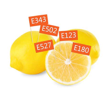Fresh lemons with E numbers on white background. Harmful food additives