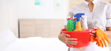Young chambermaid holding cleaning supplies in hotel room, closeup view with space for text. Banner design Stock Photo