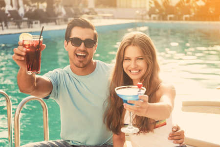 Happy young couple with fresh summer cocktails relaxing near swimming pool Stockfoto