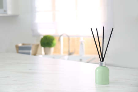 Aromatic reed air freshener on light table indoors. Space for text