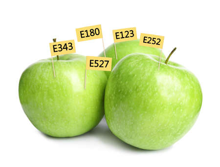 Fresh apples with E numbers on white background. Harmful food additives