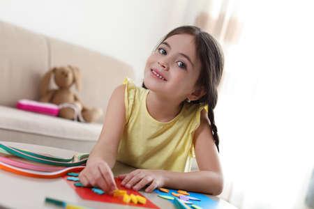 Kleines Mädchen, das drinnen am Tisch quillt. Kreatives Hobby