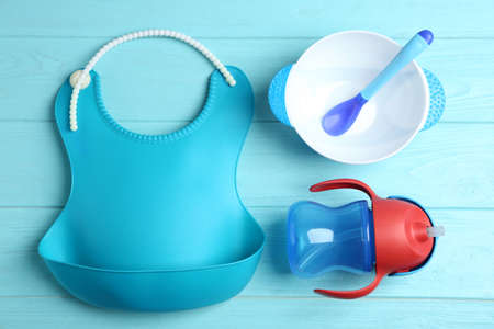 Set of plastic dishware and silicone bib on light blue wooden table, flat lay. Serving baby food