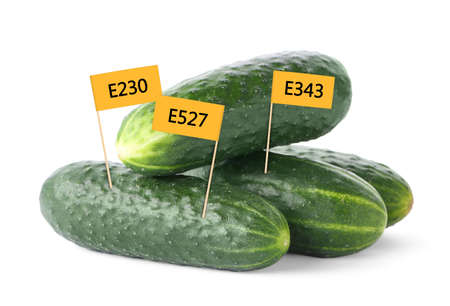 Fresh cucumbers with E numbers on white background. Harmful food additives