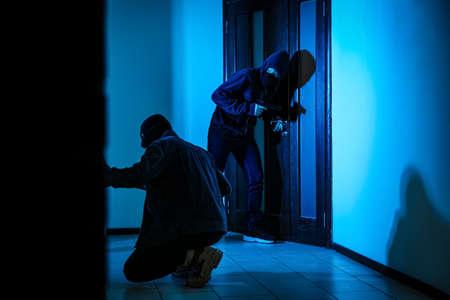 Dangerous criminals with gun and crow bar intruding into apartment
