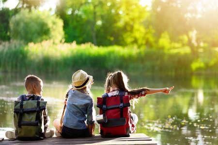 School holidays. Group of children sitting on wooden pier near river  Banco de Imagens