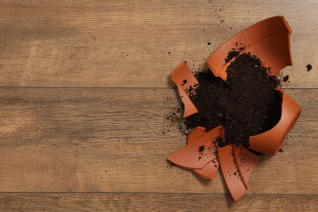 Broken terracotta flower pot with soil on wooden background, flat lay. Space for text