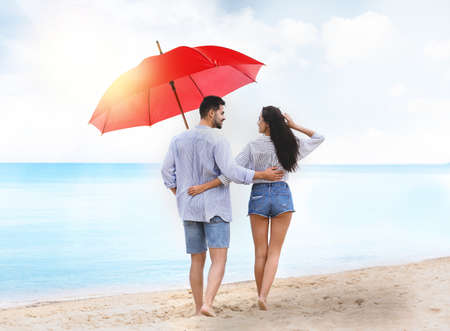 Happy young couple with umbrella for sun protection walking on beach near sea