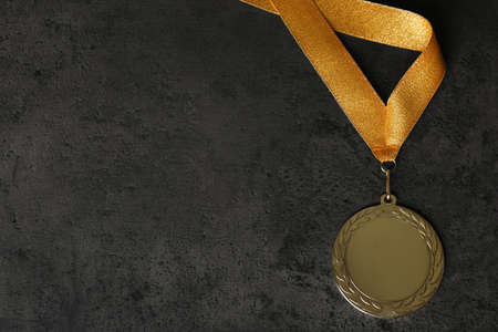 Gold medal on grey stone background, top view. Space for design Banco de Imagens