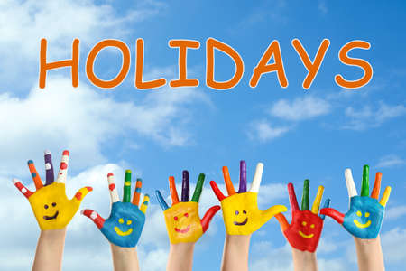 School holidays. Children with painted palms and blue beautiful sky on background, closeup Stockfoto
