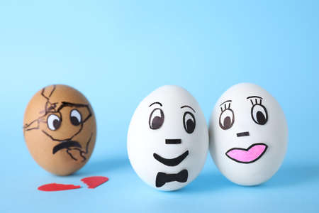 Eggs with drawn faces on light blue background. Concept of jealousy