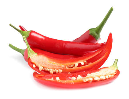 Cut and whole red hot chili peppers on white background