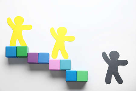 Human paper figures and stairs made of cubes on white background, flat lay. Concept of jealousy Stock Photo