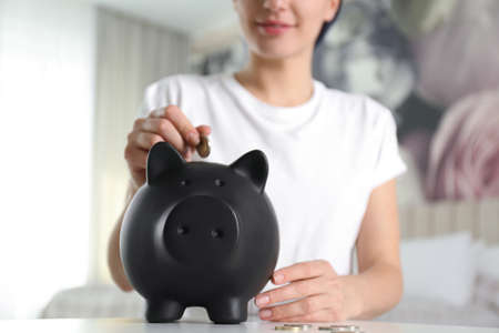 Woman putting money into piggy bank at white table indoors, closeup