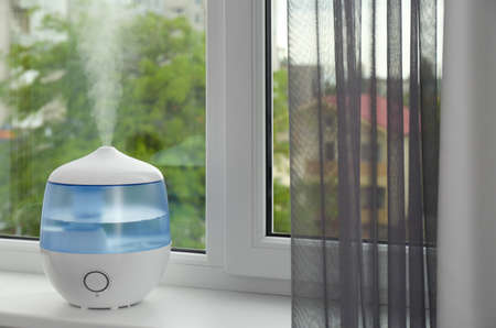 Modern air humidifier on windowsill indoors. Space for text