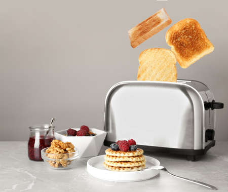 Slices of grilled wheat bread flying out of toaster on light marble table  Reklamní fotografie