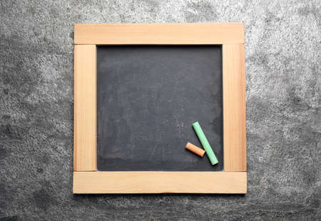 Empty blackboard with chalk on grey stone background, top view. Space for text