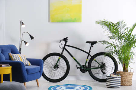 Modern bicycle and comfortable armchair in stylish living room interior