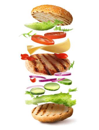 Délicieux hamburger avec différents ingrédients volants sur fond blanc