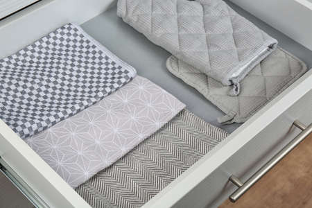Open drawer with folded towels and oven mittens. Order in kitchen 写真素材