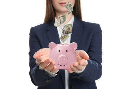 Young woman and American dollars falling into piggy bank on white background, closeup
