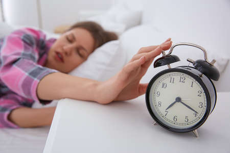 Sleepy young woman turning off alarm clock at home in morning, focus on hand Banco de Imagens