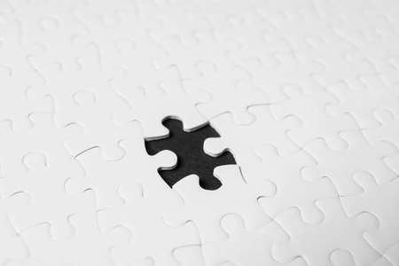 Blank white puzzle with missing piece on black background