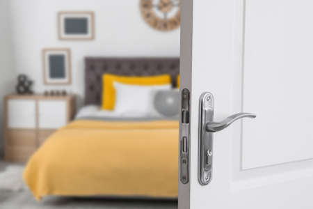 White door open into modern hotel room, closeup