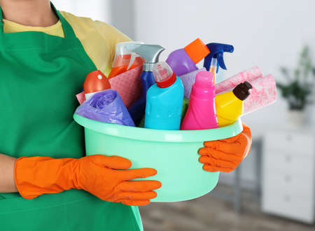 Woman holding basin with cleaning supplies in office, closeup