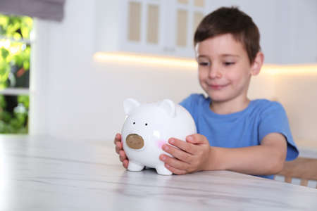 Little boy with piggy bank at marble table indoors