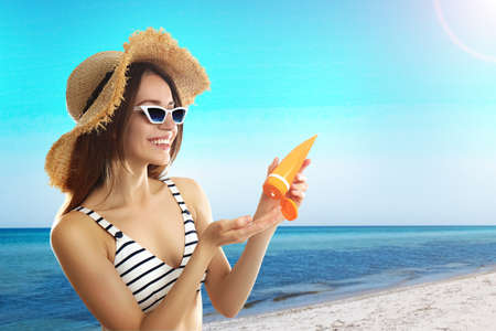 Young woman applying sun protection cream at beach, space for text