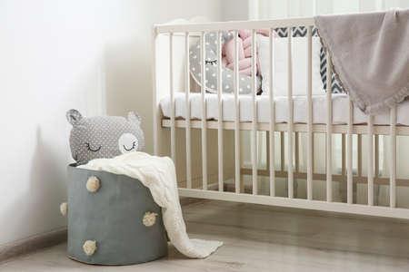 Basket with toy near crib in baby room. Interior design Standard-Bild