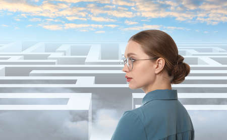 Young businesswoman looking for way out of maze