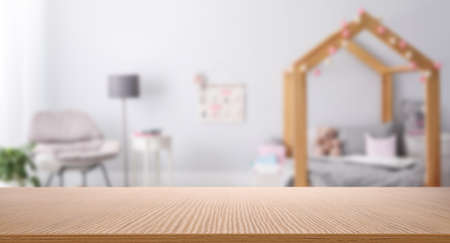 Empty wooden table in baby room interior