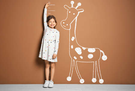 Little girl measuring height and drawing of giraffe near brown wall Stock Photo