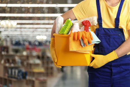 Male janitor with cleaning supplies in shopping mall, closeup. Space for text