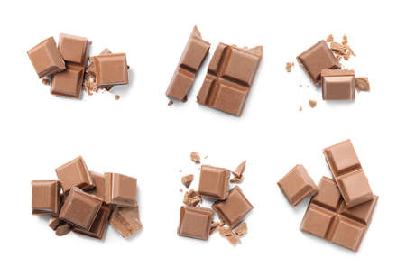 Set with pieces of milk chocolate on white background, top view
