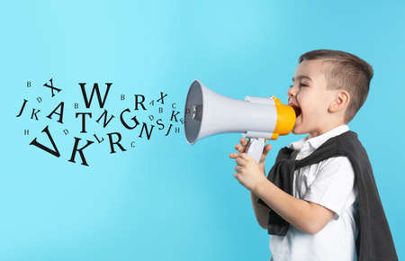 Cute funny boy with megaphone and letters on light blue background. Speech therapy concept Reklamní fotografie