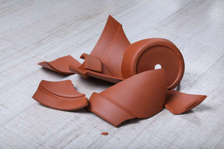 Broken terracotta flower pot on wooden background