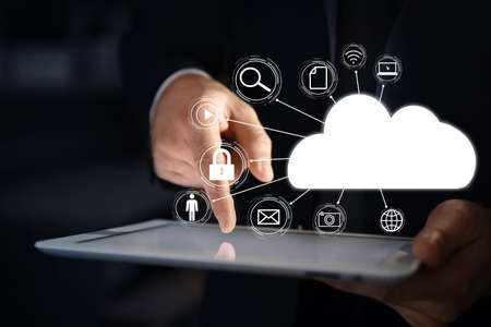 Cloud computing and storage concept. Businessman using tablet on dark background, closeup 스톡 콘텐츠