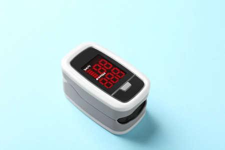 Modern fingertip pulse oximeter on light blue background, closeup